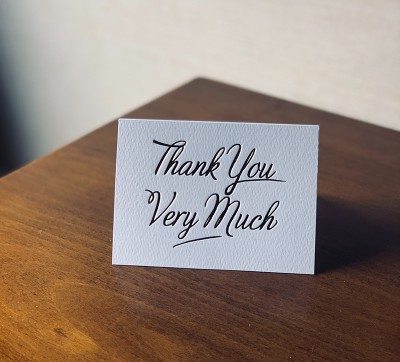 A thank you card sitting on a table.